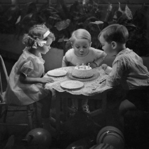 ca. 1934 --- Three children blowing out candles on birthday cake --- Image by © Condé Nast Archive/CORBIS